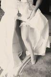 Bruden visar en snöra åtstrumpeband som upp stiger en bröllopsklänning Arkivfoto