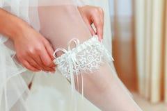 Bruden visar oss vad är under henne klänningen Arkivbild