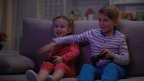 Bruder, der Schwestersteuerknüppel, Kinder spielen Videospiel nachts, Beziehungen nimmt stock video