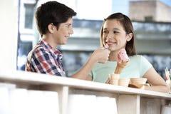 Bruder-Feeding Strawberry Ice-Creme zur Schwester At Counter Lizenzfreies Stockfoto