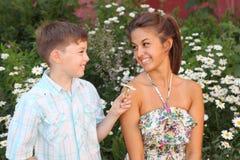 Bruder geben Blumenschwester Stockfotos