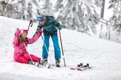 Bruder hilft seiner Schwester, vom Skigelände mit Skis aufzustehen Lizenzfreies Stockfoto