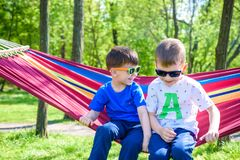 Bruder und Junge, die in der Hängematte an den Ferien sich entspannen Stockfotos
