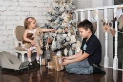 Bruder und kleine Schwester nahe bei dem Weihnachtsbaum Lizenzfreie Stockfotografie