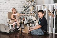 Bruder und kleine Schwester nahe bei dem Weihnachtsbaum Stockbild