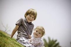 Bruder und Schwester auf dem Gras Stockbild
