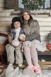 Bruder und Schwester auf einer Bank vor dem Haus im Winter Stockbild