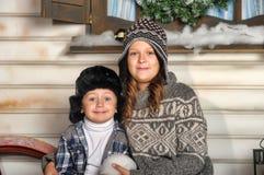 Bruder und Schwester auf einer Bank vor dem Haus im Winter Lizenzfreie Stockfotos
