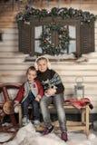 Bruder und Schwester auf einer Bank vor dem Haus im Winter Stockbilder
