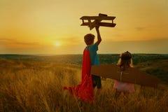 Bruder und Schwester in den Klagen von Superheldpiloten bei Sonnenuntergang Lizenzfreies Stockfoto