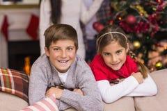 Bruder und Schwester, die auf der Couch sich lehnen Stockfotos