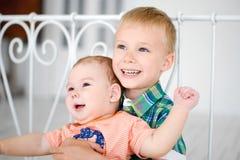 Bruder und Schwester, die das Sitzen auf einem Bett spielen Stockfotografie