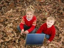 Bruder und Schwester, die in den Blättern mit Laptop sitzen Lizenzfreie Stockfotos