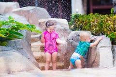 Bruder und Schwester, die draußen mit Wasserhahn spielen Stockfotografie