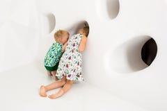 Bruder und Schwester, die in einem weißen Studio spielen und lächeln Lizenzfreie Stockbilder