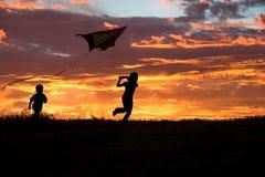 Bruder und Schwester, die einen Drachen fliegen. Stockfotografie