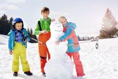 Bruder und Schwester, die einen Schneemann errichten lizenzfreies stockbild