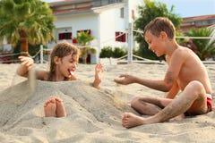 Bruder und Schwester, die im Sand auf Strand spielen stockbild