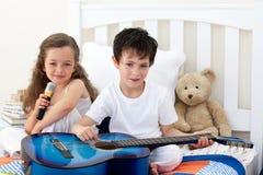 Bruder und Schwester, die im Schlafzimmer spielen lizenzfreies stockbild