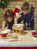 Bruder und Schwester, die Lebkuchenhaus verzieren stockfoto