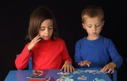 Bruder und Schwester, die mit einem Puzzlespiel spielen stockfoto