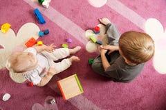 Bruder und Schwester, die mit Spielzeugblöcken spielen Stockbilder