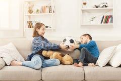 Bruder und Schwester, die zu Hause Fußball halten Lizenzfreie Stockfotos