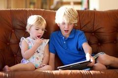 Bruder und Schwester, die zu Hause mit Tabletten-PC spielen Lizenzfreies Stockbild