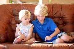 Bruder und Schwester, die zu Hause mit Tabletten-PC spielen Stockfoto