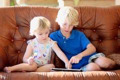 Bruder und Schwester, die zu Hause Tabletten-PC verwendet Stockbild