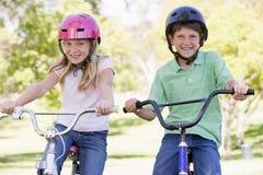 Bruder und Schwester draußen auf dem Fahrradlächeln Stockfoto