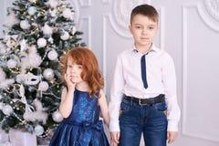 Bruder und Schwester Es gibt 3 Mädchen und ihre Mutter, die auf der orange Couch sitzen Weihnachtsinnenraum Kleine Kinder Lizenzfreie Stockfotografie