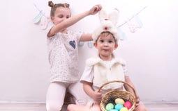Bruder und Schwester feiern Ostern Der Junge wird in einem Kaninchenkostüm gekleidet und ein korunzku mit Ostereiern hält Lizenzfreies Stockbild