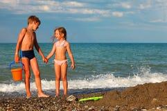 Bruder und Schwester halten Hände an und stehen auf Strand lizenzfreie stockfotos