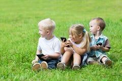 Bruder und Schwester im Garten, der auf dem Gras sitzt Lizenzfreies Stockbild
