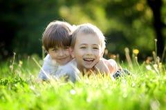 Bruder und Schwester im Gras Stockfotografie
