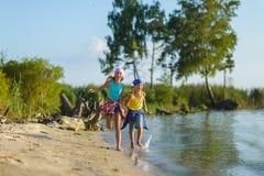 Bruder und Schwester laufen gelassen entlang Strand Feiertag und Reisekonzept Lizenzfreie Stockfotos