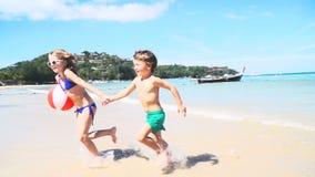 Bruder und Schwester laufen Hand in Hand vom Meer auf dem Knall Tao-Strand stock footage