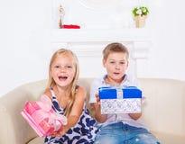 Bruder und Schwester mit Geschenken stockfotos
