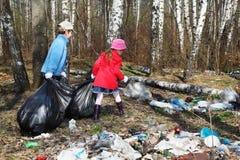 Bruder und Schwester montieren Abfall im Park Stockbild