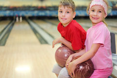 Bruder und Schwester sitzen im Bowlingspielklumpen Stockfotografie