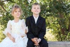 Bruder und Schwester sitzen und lächeln Lizenzfreie Stockfotos