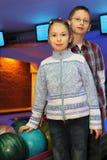 Bruder und Schwester stehen nahe Kugeln für Bowlingspiel stockbilder