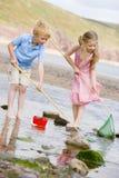 Bruder und Schwester am Strand mit Netzen und Eimer Lizenzfreie Stockfotos