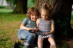 Bruder und Schwester von 8-9 Jahren spielen mit Leidenschaft auf der Tablette Stockfotografie