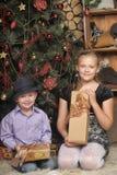 Bruder und Schwester am Weihnachtsbaum Stockfotografie