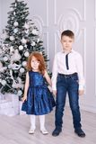 Bruder und Schwester Weihnachtsinnenraum Es gibt 3 Mädchen und ihre Mutter, die auf der orange Couch sitzen Kleine Kinder Stockfotos