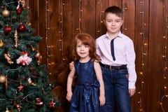 Bruder und Schwester Weihnachtsinnenraum Kleine Kinder Es gibt 3 Mädchen und ihre Mutter, die auf der orange Couch sitzen Stockfoto