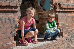Bruder und Schwester wurden allein infolge der militärischen Konflikte und der Naturkatastrophen gelassen Kinder in ruiniert und  lizenzfreies stockfoto