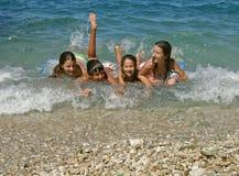 Bruder und Schwestern genießen auf Wellen Stockbild